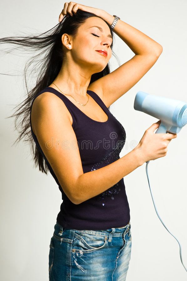 La fille avec le sèche-cheveux image stock
