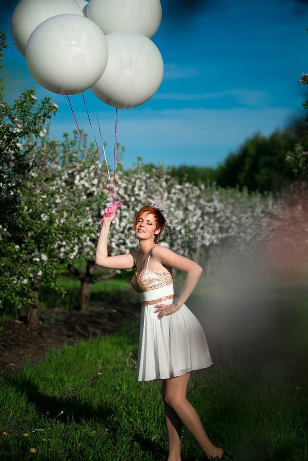 La fille avec le sourire tenant un groupe d'hélium blanc monte en ballon photographie stock