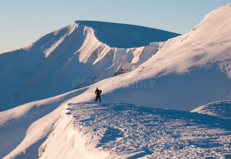 La fille avec le surf des neiges se tient sur une montagne et admire de belles vues images libres de droits