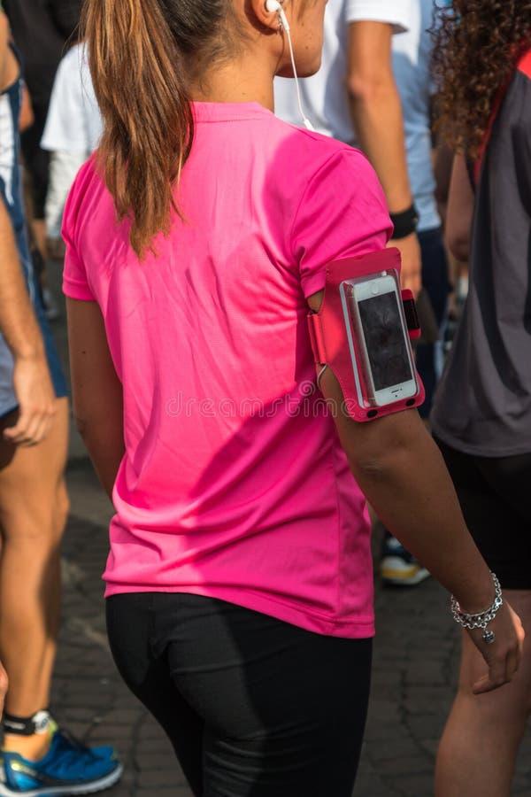 La fille avec le T-shirt rose et le brassard de Smartphone enferment l'attente au RU photo stock
