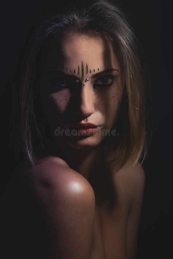 La fille avec le tribal composent dans contrasté images libres de droits