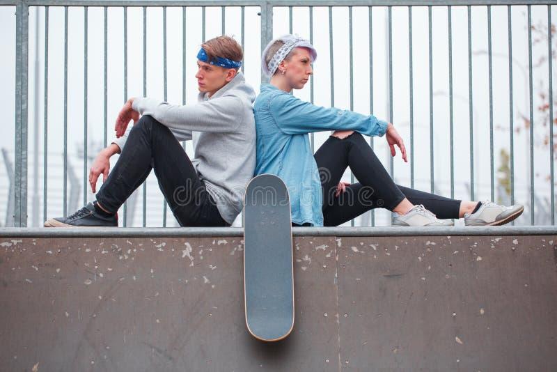 La fille avec le type s'asseyant de nouveau au regard arrière dans différentes directions sur la dispersion en parc de patin images libres de droits