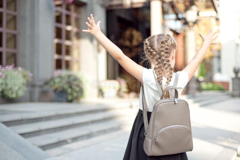 La fille avec les cheveux blonds se réjouit dans le renvoi à l'école par derrière photo libre de droits