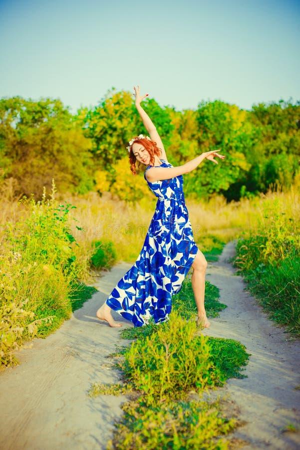 La fille avec les cheveux rouges danse image stock