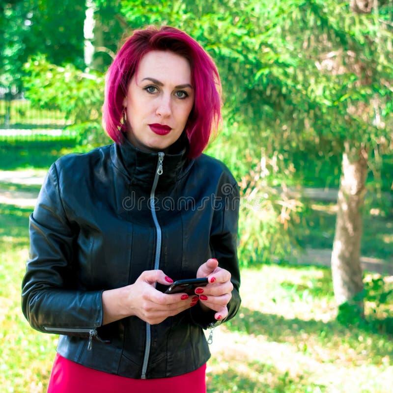 La fille avec les cheveux rouges fait une exposition avec de grandes bulles de savon ou la pose sur un fond bleu de mur photo libre de droits