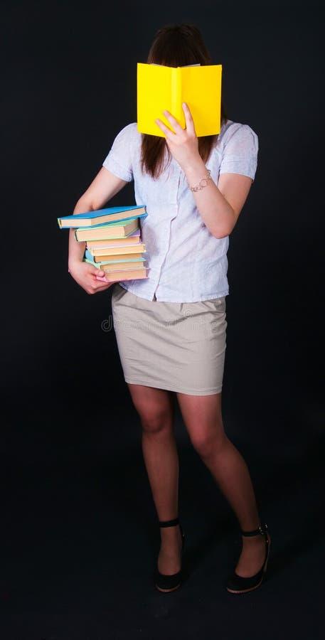 La fille avec les livres multicolores photos stock