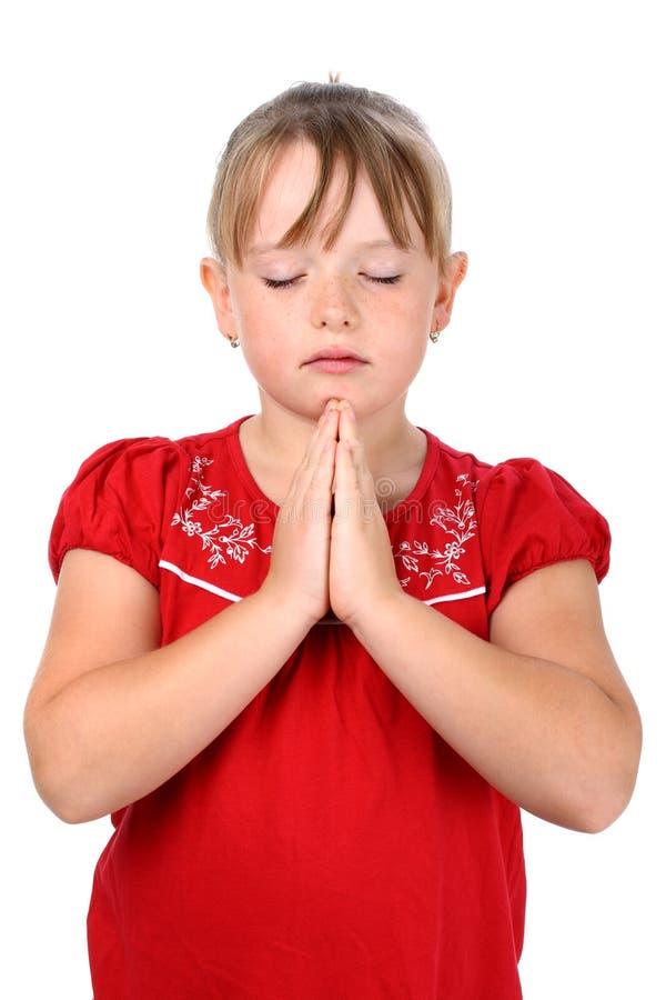 La fille avec les mains étreintes et observe la prière fermée photographie stock libre de droits