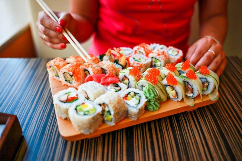 La fille avec les mains bien-toilett?es tient des baguettes pour des sushi La fille mange un grand ensemble de sushi photo stock
