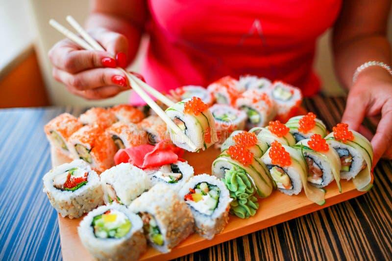 La fille avec les mains bien-toilett?es tient des baguettes pour des sushi La fille mange un grand ensemble de sushi images stock