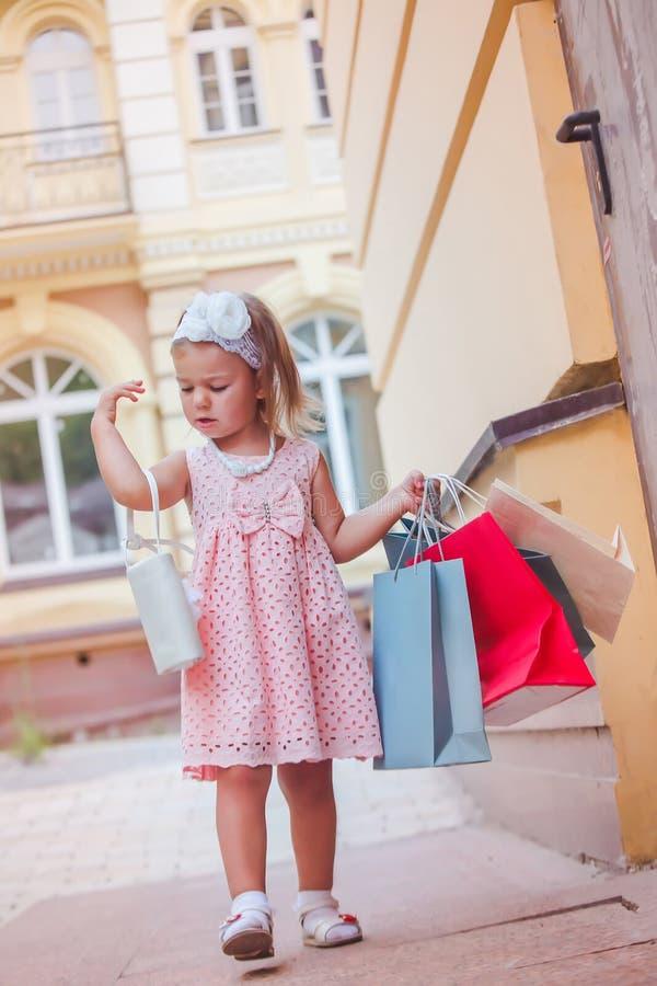 La fille avec les paniers marqués ajuste sa bourse sur son épaule L'enfant heureux pendant le week-end va faire des emplettes dan photo stock