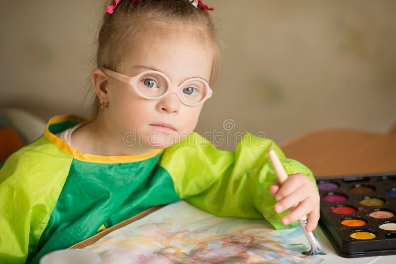 La fille avec la trisomie 21 dessine des peintures image libre de droits