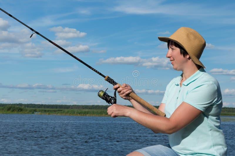La fille avec un chapeau pêche sur une rivière un jour ensoleillé, plan rapproché photo libre de droits