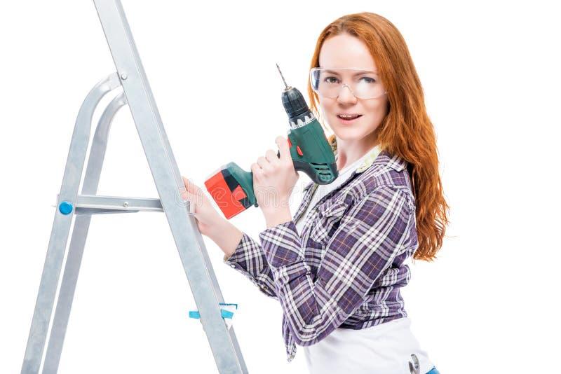 la fille avec un outil se tient sur un escabeau photographie stock