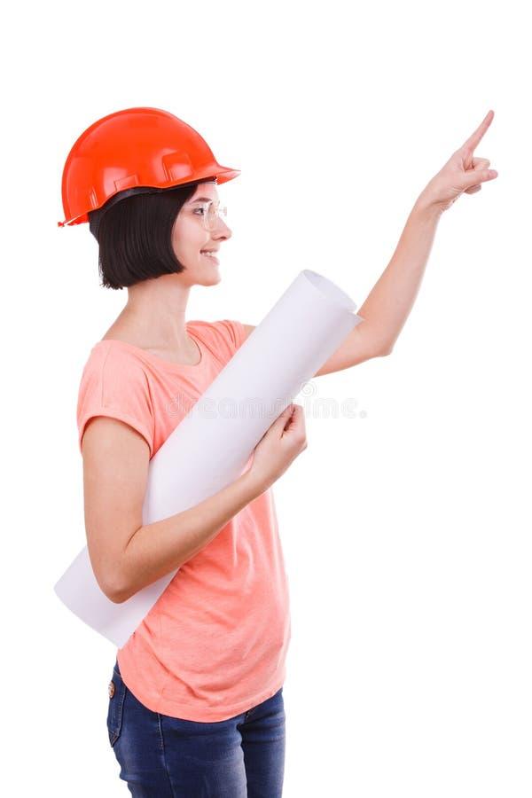 La fille avec un papier dans sa main, dans un casque montrant quelque part avec son doigt sur un blanc a isolé le fond photos stock