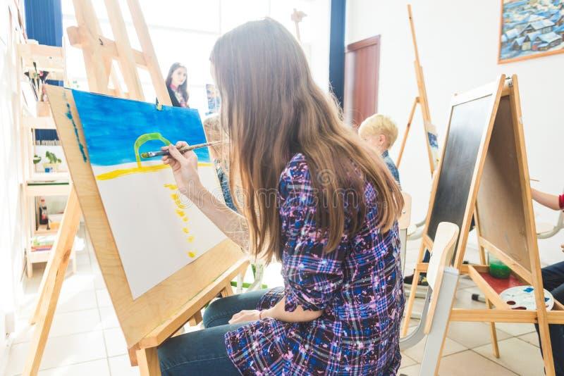 La fille avec un professeur dans le groupe de l'étudiant préscolaire a reposé le dessin une image Peinture sur le maelbert, la pa photographie stock