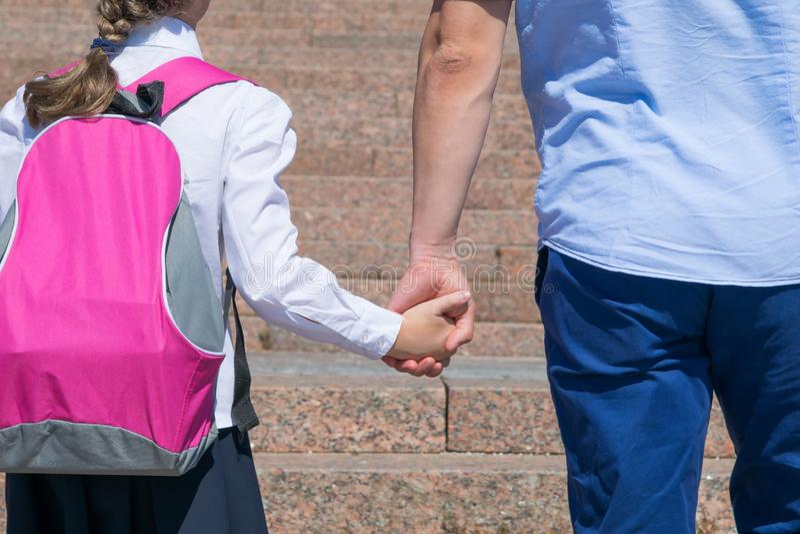 La fille avec un sac à dos rose, se lève les escaliers, tenant sa main de pères images libres de droits