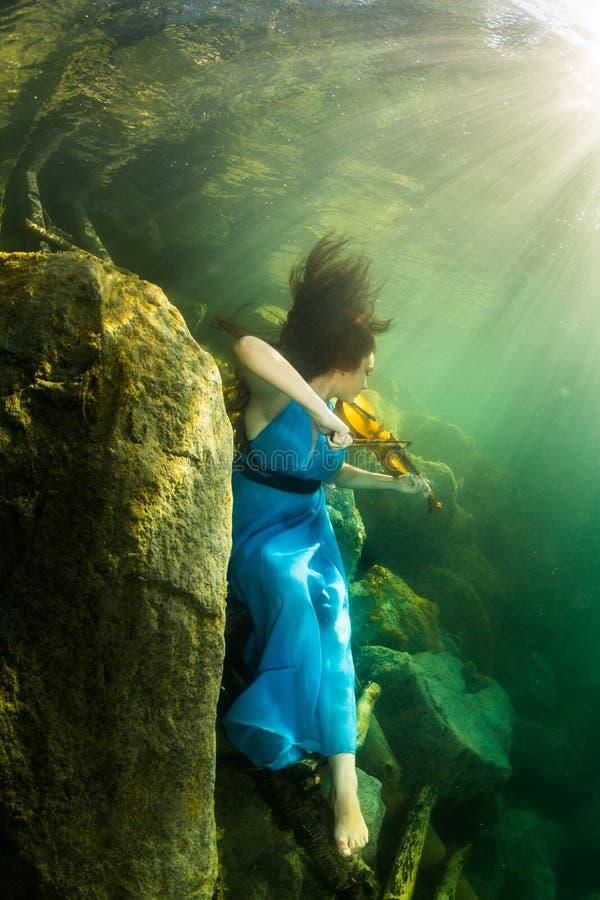 La fille avec un violon sous l'eau photo libre de droits