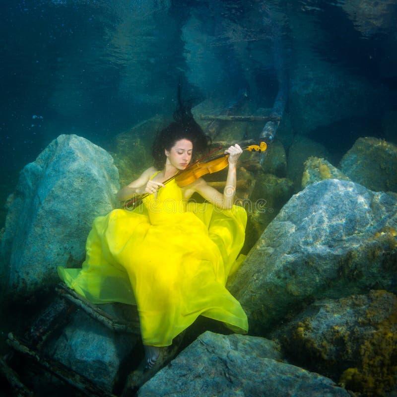 La fille avec un violon sous l'eau photos stock