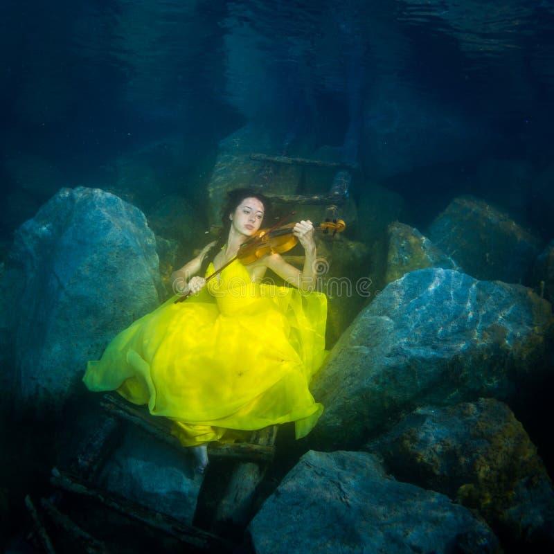 La fille avec un violon sous l'eau image libre de droits