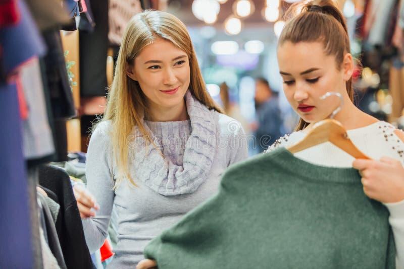 La fille avec une amie dans un magasin d'habillement a trouvé un chandail vert qu'elle a aimé images libres de droits