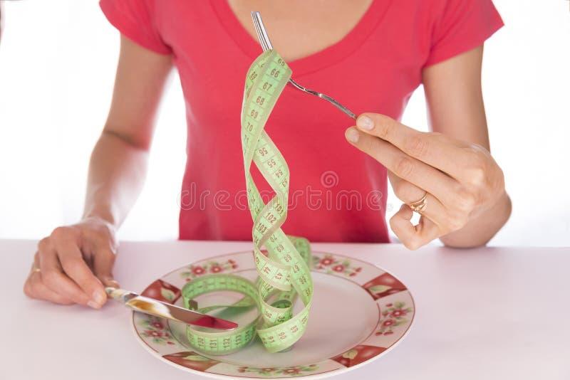 La fille avec une fourchette et un couteau image stock