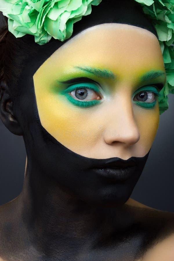La fille avec vert et noir créatifs composent et des fleurs photographie stock
