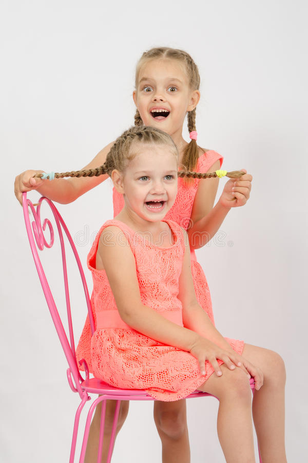 La fille ayant l'amusement tenant l'autre fille tresse des cheveux photo libre de droits