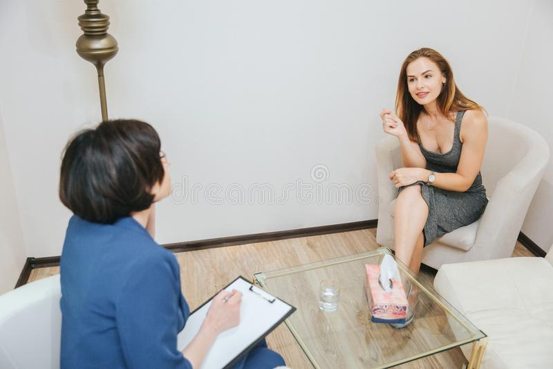 La fille belle et gentille s'assied devant le thérapeute et écoute elle très soigneusement Elle la croise photo libre de droits