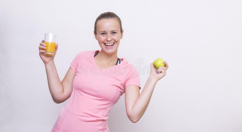 La fille blanche dans un dessus rose de sports tient un verre de jus et d'AP photo stock
