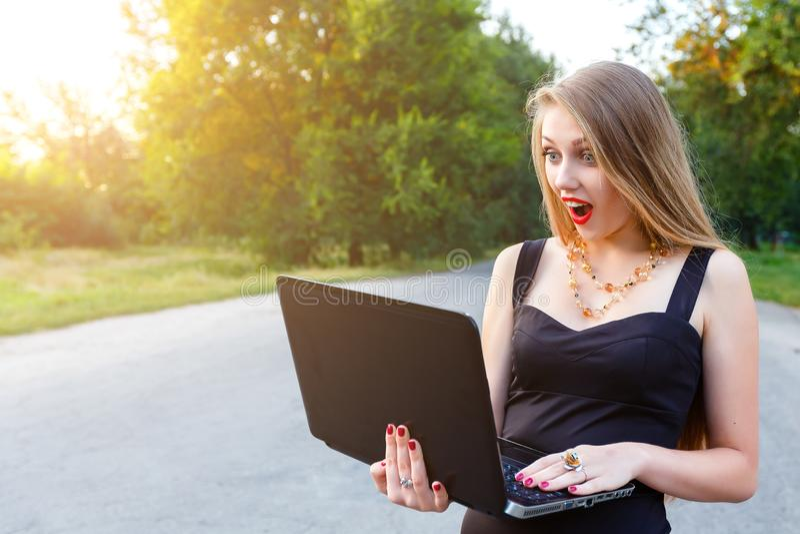 La fille blonde étrange regarde l'ordinateur portable Travail femelle de directeur au jour d'été ensoleillé dehors image libre de droits