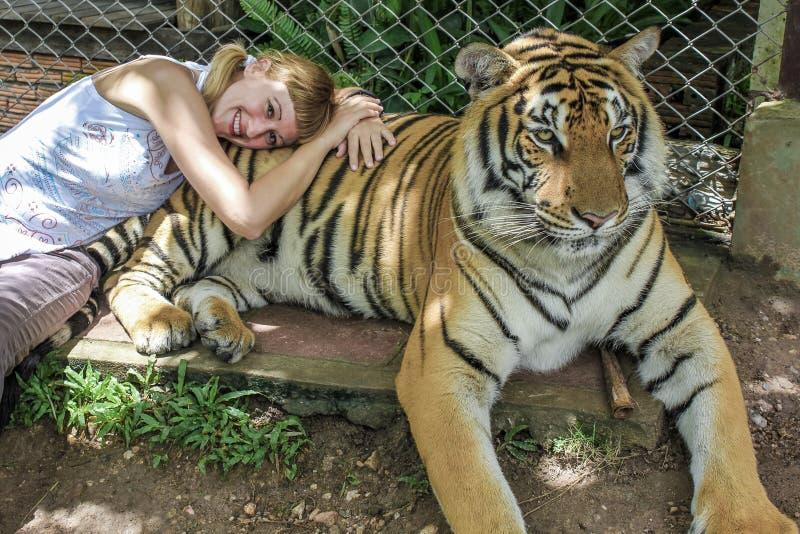 La fille blonde avec des tresses se couche sur un tigre courageux thaïlandais photographie stock libre de droits