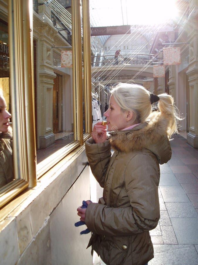 La fille blonde avec les cheveux blonds peint ses lèvres avec le rouge à lèvres près de la fenêtre images libres de droits