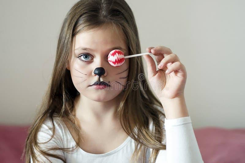 La fille blonde avec un maquillage imitant un chat tient dans sa main des chups d'un chupa images libres de droits