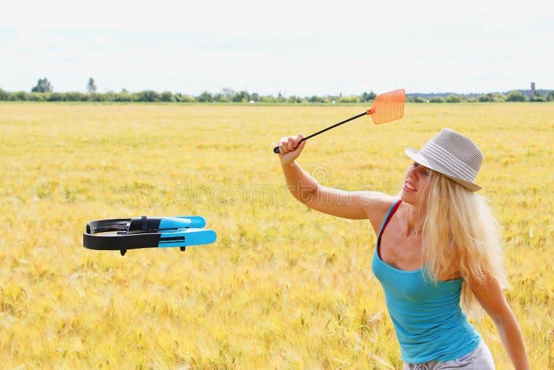 La fille blonde avec une tapette de mouche conduit loin le bourdon image stock