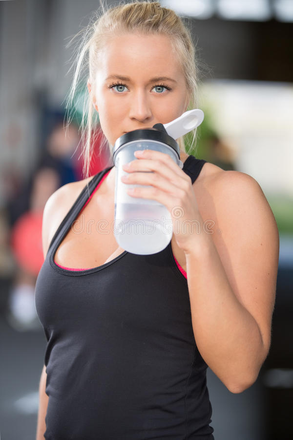 La fille blonde boit l'eau au centre de gymnase de forme physique photos stock