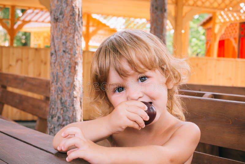 La fille blonde bouclée mange une prune délicieuse dehors images libres de droits
