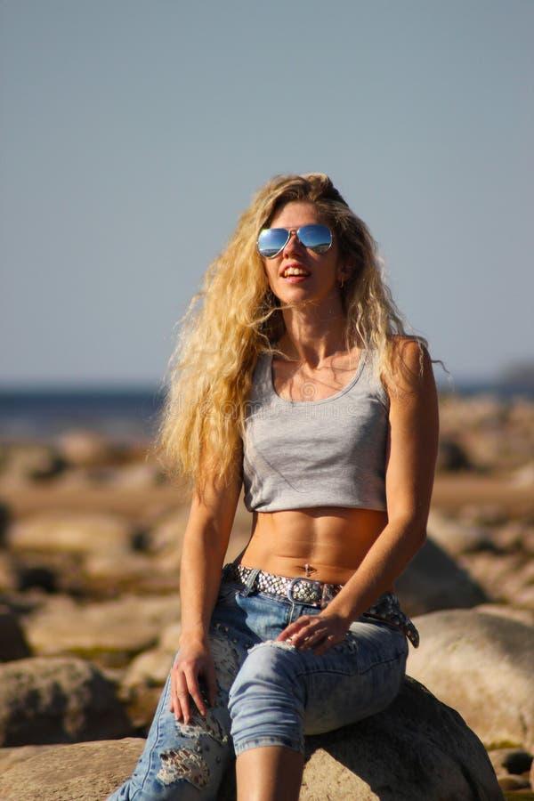 La fille blonde bronz?e dans les lunettes de soleil et des jeans s'assied sur les roches sur la plage un jour ensoleill? image libre de droits