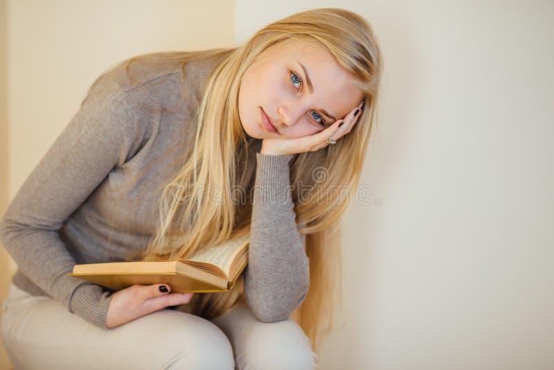 La fille blonde buvant de son café, mangent des biscuits et ont lu un livre photos stock