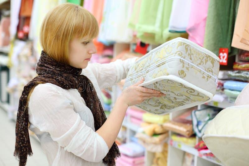 La fille blonde choisit le matelas dans le système image stock