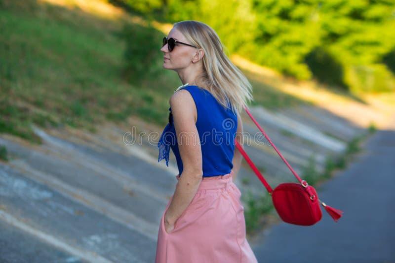 La fille blonde dans des lunettes de soleil de port bleues de jupe supérieure et rose-clair avec un petit sac d'épaule rouge rega image libre de droits