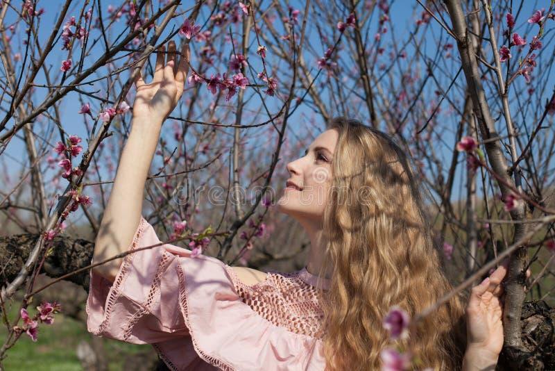 La fille blonde dans la robe rose rassemble des fleurs dans le jardin image stock