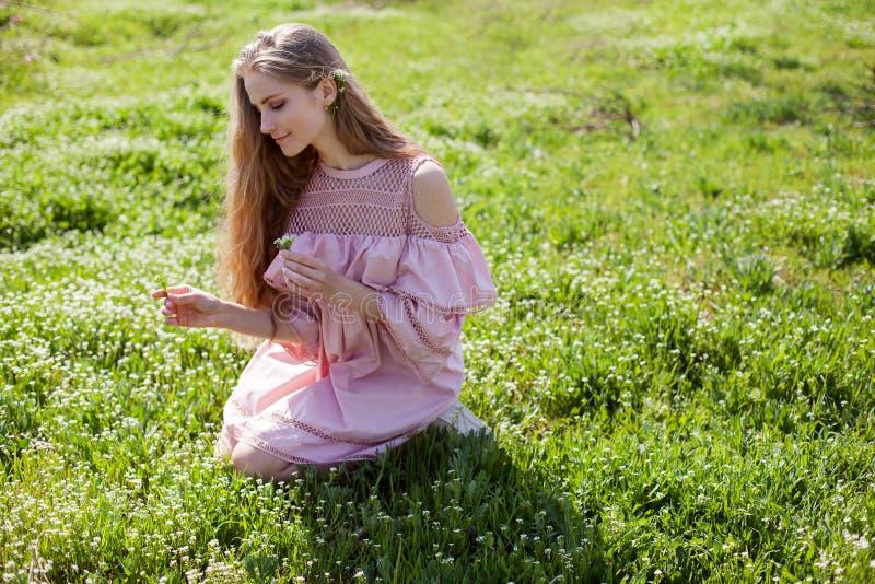 La fille blonde dans la robe rose rassemble des fleurs dans le jardin photos stock