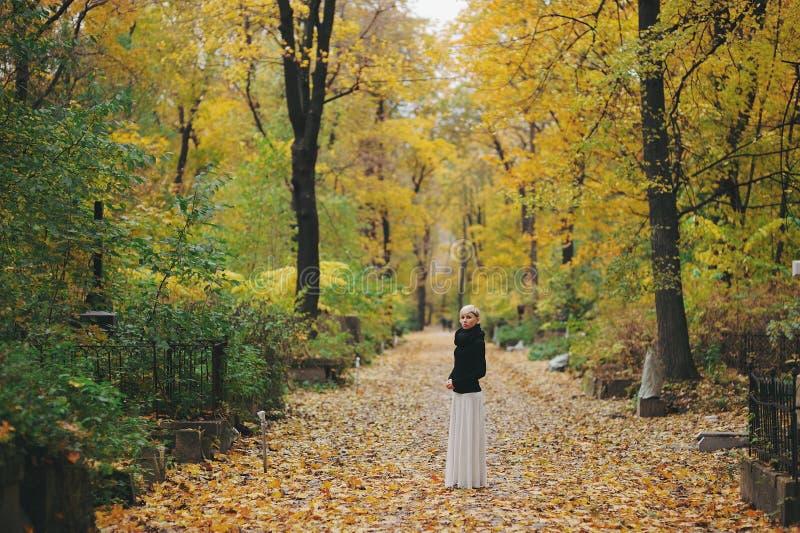 La fille blonde dans un chemisier noir et le blanc bordent la position en parc dans la forêt d'automne photo libre de droits
