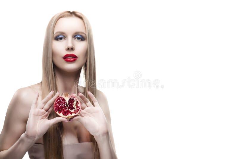 La fille blonde de belles jeunes lèvres rouges aux cheveux longs tient une moitié de photo stock
