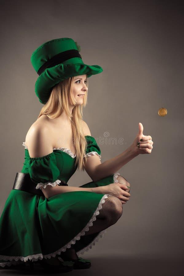 La fille blonde de sourire dans le lutin vêtx avec une pièce de monnaie photographie stock libre de droits