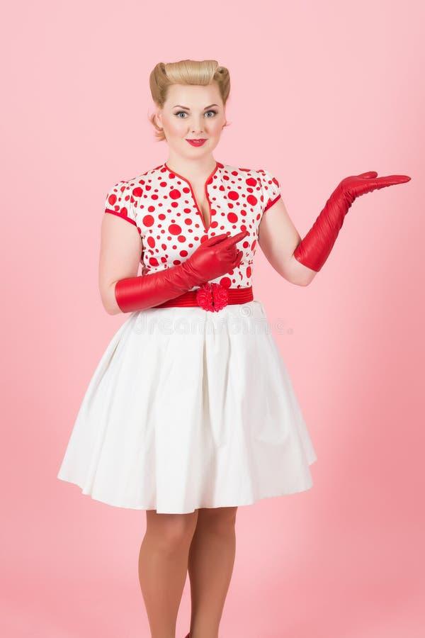 La fille blonde font faire de la publicité à la main dans les gants rouges La belle femme démontrent l'endroit en main Jolies ven photo libre de droits