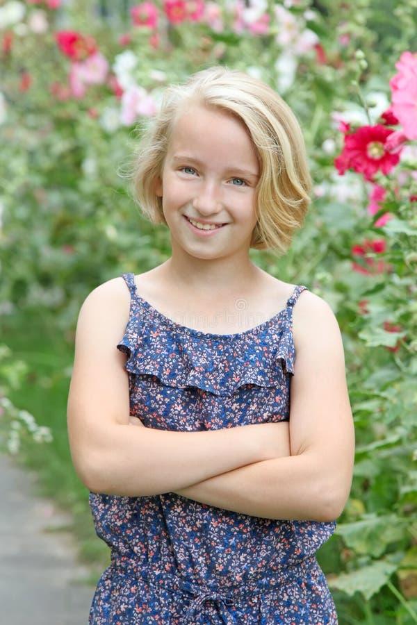 La fille blonde gaie sur une promenade dans le jardin sur un fond de la floraison fleurit photographie stock libre de droits