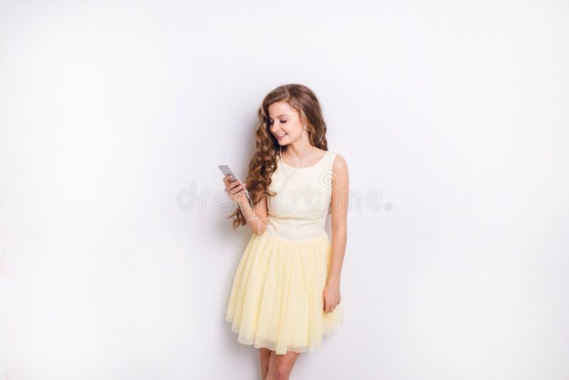 La fille blonde mignonne écoutant la musique sur des écouteurs sur le smartphone a l'amusement Elle sourit largement et joue avec photo libre de droits