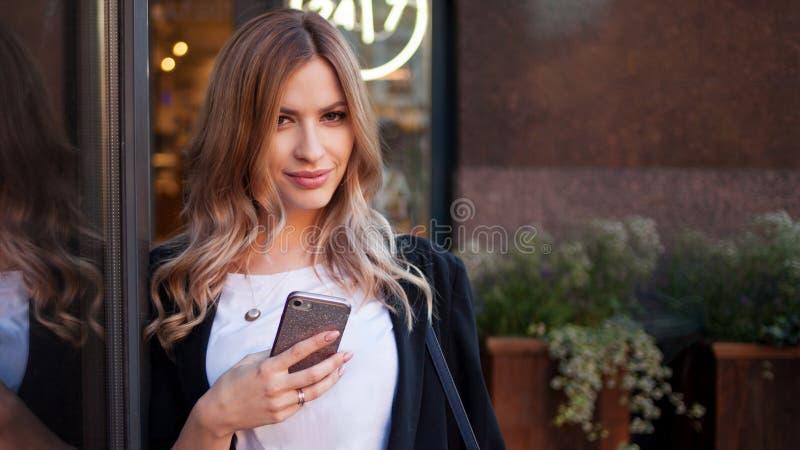 La fille blonde mignonne utilise son smartphone La femme marche autour de la ville images stock