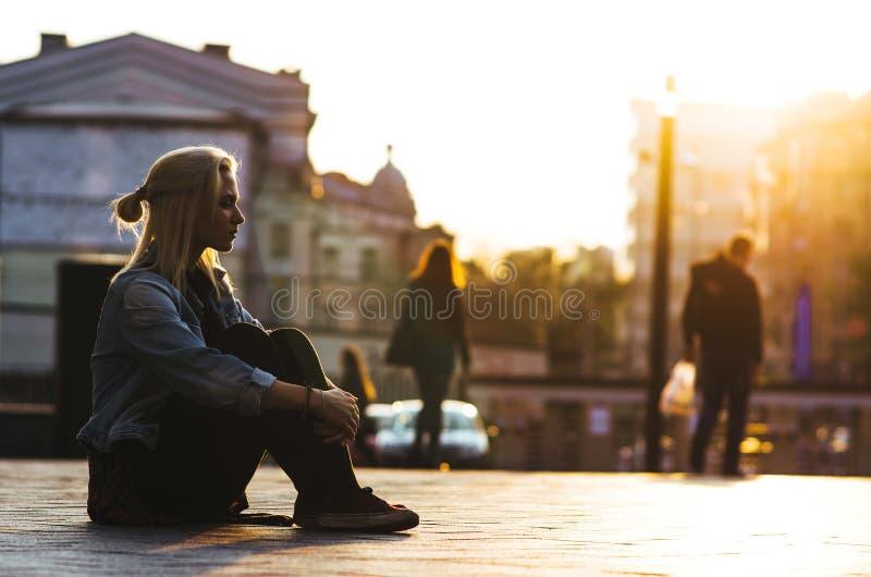 la fille blonde s'assied sur le fond de la ville et du coucher du soleil image libre de droits